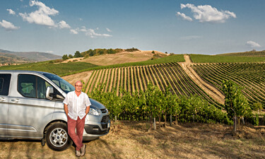 Tuscany tour guide Sergio with his van in a Chianti vineyard