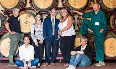 The staff at a Tuscan winery in front of barrels